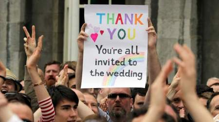 A supporter holds a sign reading 'Thank You - You're All Invited to the Wedding' as he celebrates outside Dublin Castle following the result of the same-sex marriage referendum in Dublin on May 23, 2015. Ireland on Saturday became the first country in the world to approve gay marriage by popular vote as crowds cheered in Dublin in a spectacular setback for the once all-powerful Catholic Church.    AFP PHOTO /  PAUL FAITH        (Photo credit should read PAUL FAITH/AFP/Getty Images)