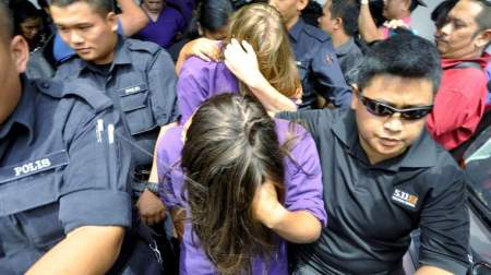 British national Eleanor Hawkins (front), along with three other tourists from Canada and the Netherlands, are escorted by police as they leave a court hearing in Kota Kinabalu, in Malaysia's eastern state of Sabah June 10, 2015. The four Western tourists who posed naked on top of Malaysia's tallest peak and were blamed by some for a deadly earthquake six days later were sentenced to three days in jail and fined on Friday after they admitted obscene behaviour. They will also be deported. Picture taken June 10, 2015. REUTERS/New Straits Times/Mohd Adam Arinin  ATTENTION EDITORS -  FOR EDITORIAL USE ONLY. NOT FOR SALE FOR MARKETING OR ADVERTISING CAMPAIGNS. THIS IMAGE HAS BEEN SUPPLIED BY A THIRD PARTY. IT IS DISTRIBUTED, EXACTLY AS RECEIVED BY REUTERS, AS A SERVICE TO CLIENTS. NO SALES. NO ARCHIVES. MALAYSIA OUT. NO COMMERCIAL OR EDITORIAL SALES IN MALAYSIA        TPX IMAGES OF THE DAY